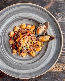 Tagliatelle preparate con peperoni di mare semi di sesamo e salsa