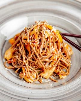Tagliatelle preparate con peperoni di pollo semi di sesamo e salsa