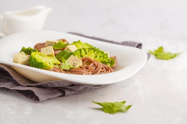 Tagliatelle vegetariane di soba con tofu e broccoli, superficie bianca. concetto di cibo vegano sano.