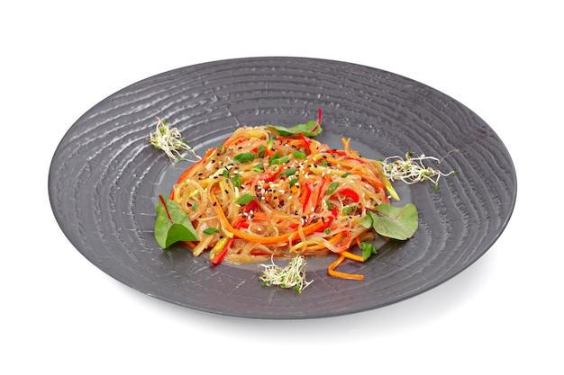 Tagliatelle wok preparate con verdure a fette su stoviglie grigie
