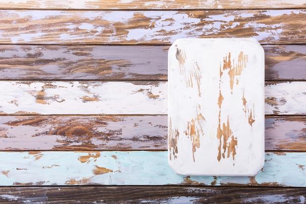 Tagliere bianco rustico sul vecchio fondo di legno multicolore della plancia. copia spazio