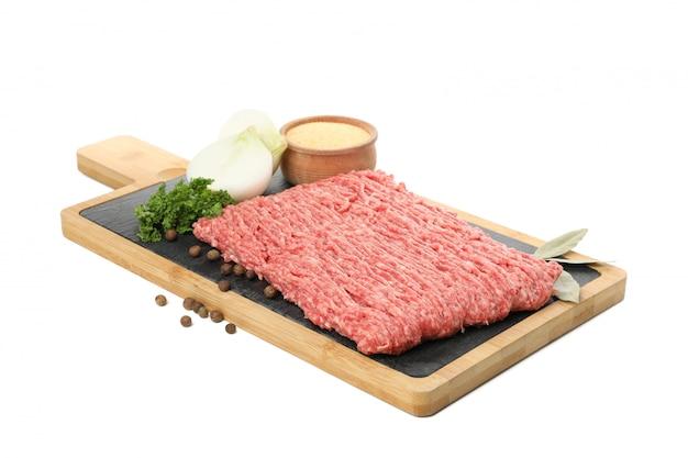 Tagliere con carne tritata e spezie isolate su bianco