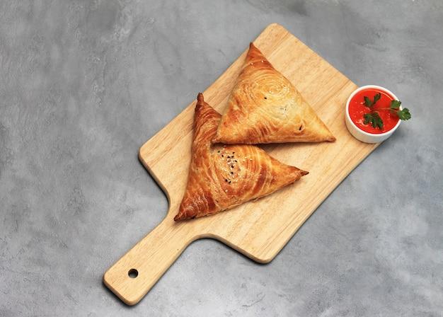Tagliere con deliziose samosa di carne e salsa rossa su grigio