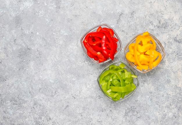 Tagliere con fette di peperoni colorati sulla superficie della luce. peperoni dolci affettati nei colori differenti, ingrediente dell'insalata di verdure, cucinante alimento sano, vista superiore