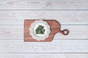 Tagliere con piatto ornamentale e foglie verdi