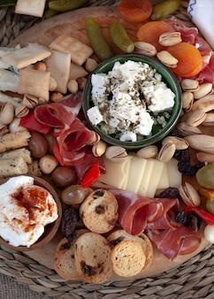 Tagliere con selezione di antipasti, varietà di formaggi, salumi, crackers, olive. pasto colorato. vista dall'alto.