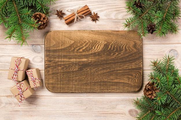 Tagliere di legno al fondo della tavola con la decorazione di natale, bordo rotondo.