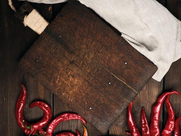 Tagliere di legno marrone vuoto molto vecchio con il tovagliolo della cucina e della maniglia