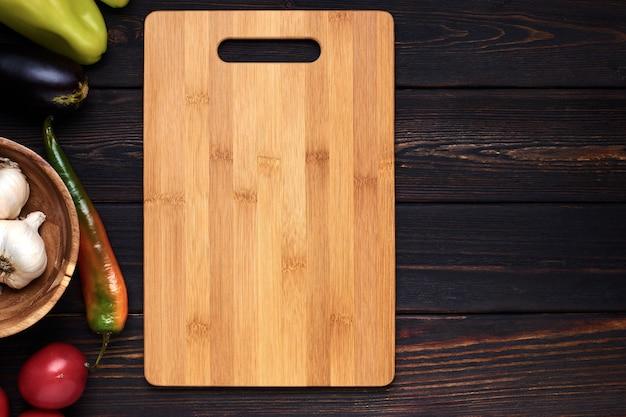 Tagliere di legno sul tavolo da cucina in legno