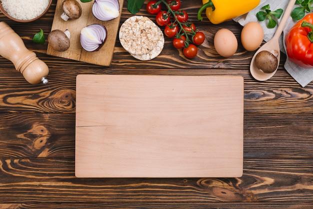 Tagliere in legno bianco con verdure crude e torta di riso soffiato sulla scrivania in legno