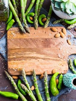 Tagliere in legno con asparagi, cornice con noci