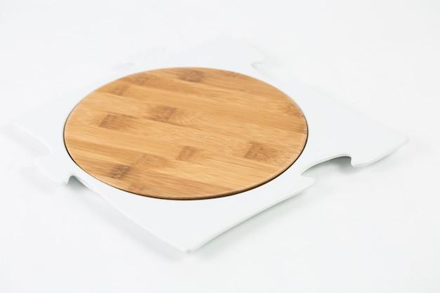 Tagliere in legno con una cornice puzzle isolata su un tavolo bianco