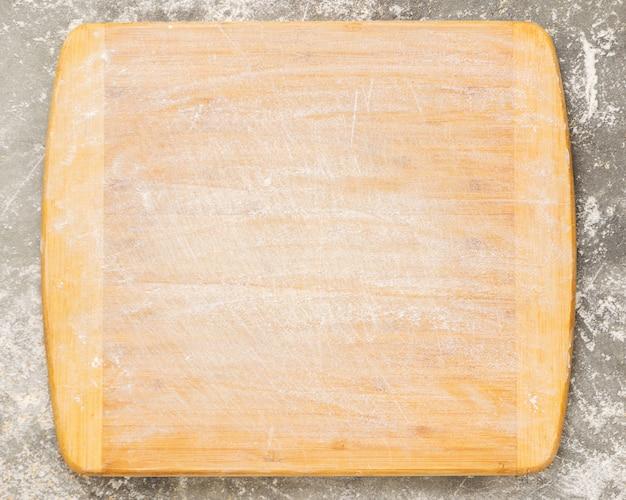 Tagliere in legno cosparso di farina vuota su uno sfondo grigio. copia spazio.