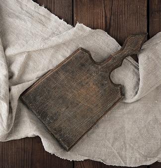 Tagliere in legno marrone molto vecchio vuoto con manico