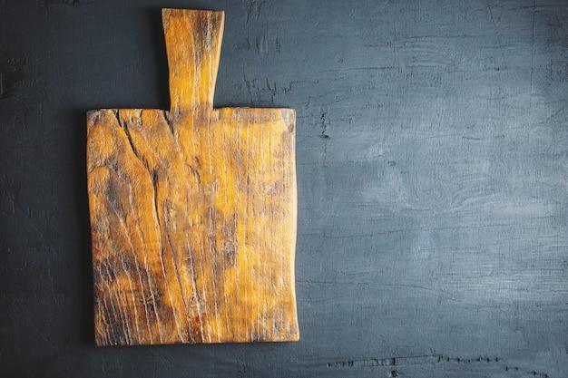 Tagliere in legno su sfondo nero