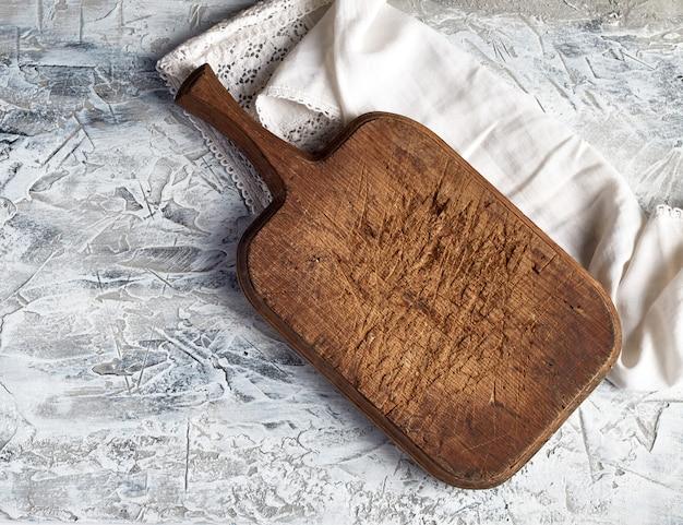 Tagliere marrone molto vecchio dell'annata e tovagliolo di cucina bianco