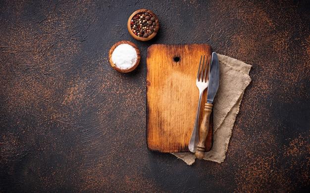 Tagliere vintage vuoto con spezie e posate