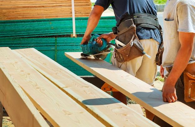 Taglio del legno con sega circolare lavoratore maschio o uomo pratico con
