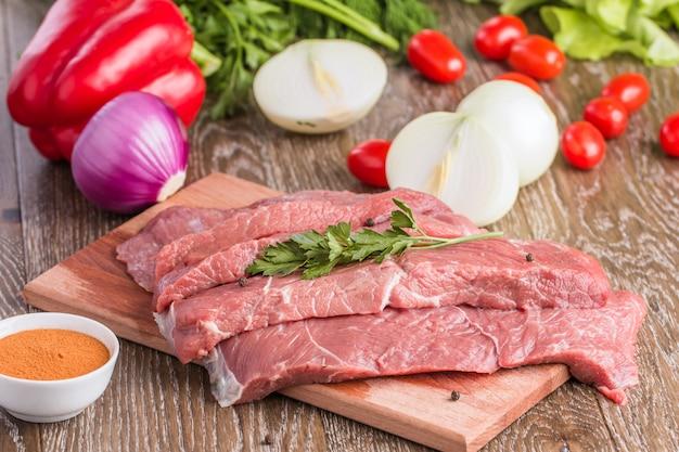 Taglio della bistecca di manzo cruda sul tagliere di legno