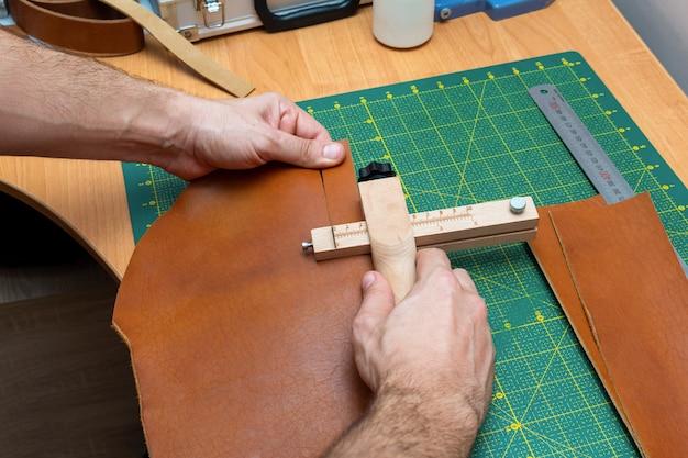 Taglio della striscia in pelle marrone per una cintura con un cutter