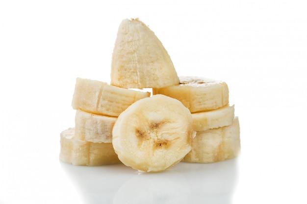 Taglio delle fette della banana isolato su bianco con la riflessione.