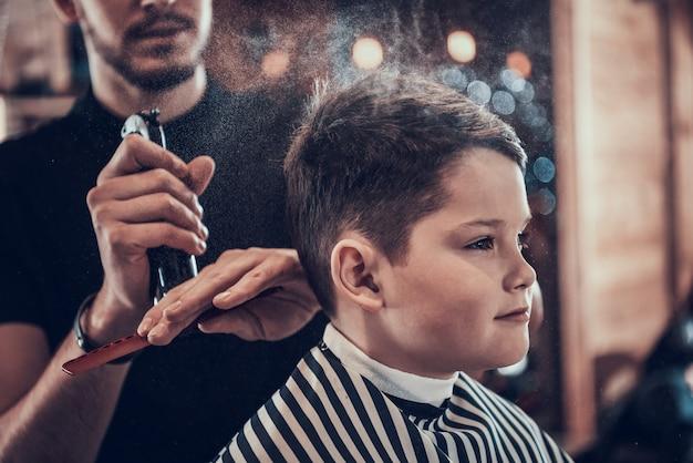 Taglio di capelli alla moda per un ragazzo in un negozio di barbiere