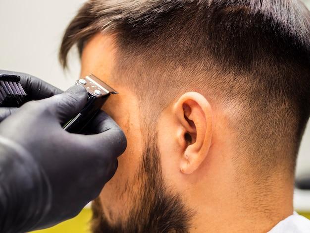 Taglio di capelli del primo piano e guanti neri