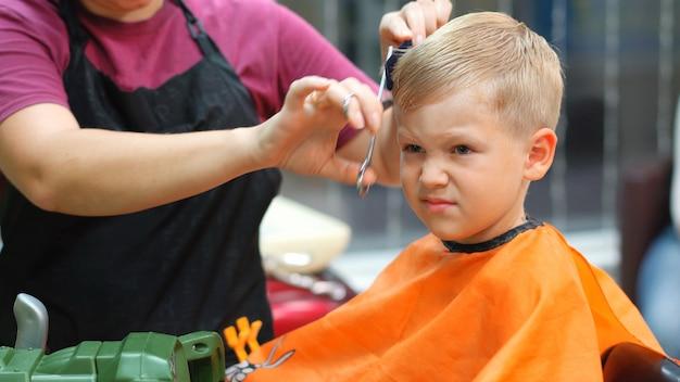 Taglio di capelli di un ragazzino in un parrucchiere per bambini
