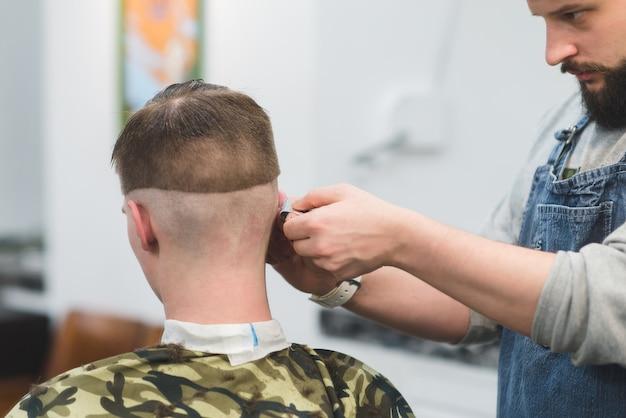 Taglio di capelli maschile nel barbiere. il barbiere fa acconciatura per il cliente. il barbiere rade il collo del rifinitore del cliente.