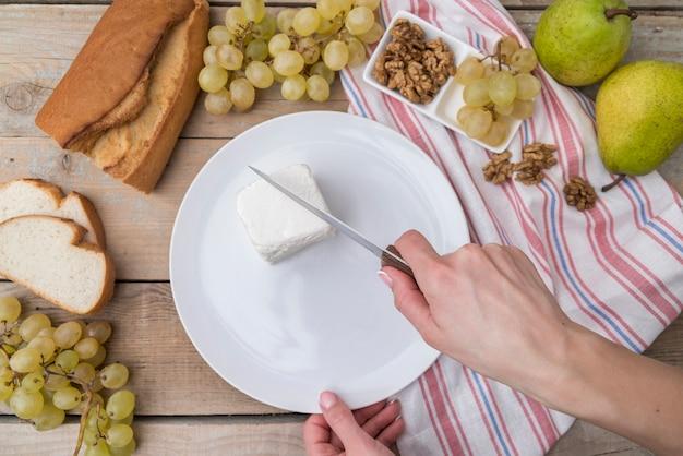 Taglio di formaggio vista dall'alto sul piatto con uva e noci