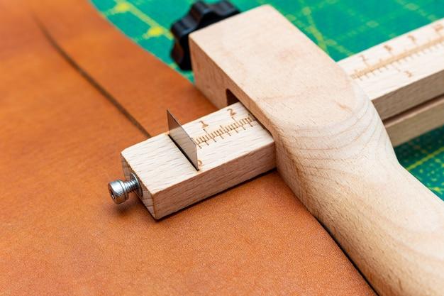 Taglio di una striscia di pelle marrone per una cintura con un taglia-strisce. officina artigianale in pelle.