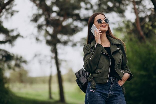 Talkimng della giovane donna al telefono in parco