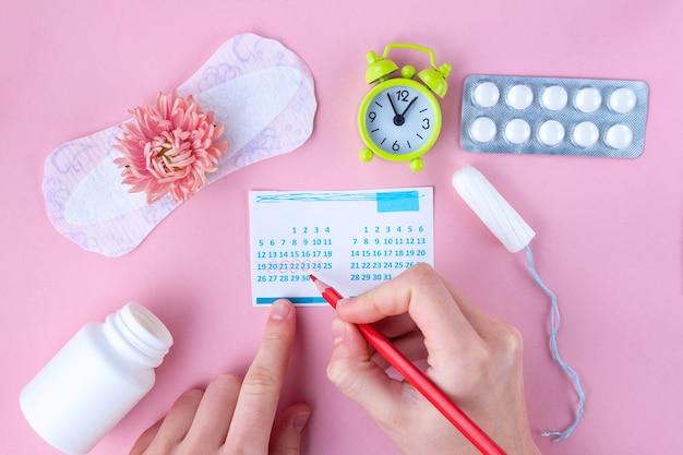 Tampone, assorbenti femminili e sanitari per giorni critici, calendario femminile, sveglia, pillole antidolorifiche durante le mestruazioni e un fiore rosa. cura dell'igiene durante le mestruazioni