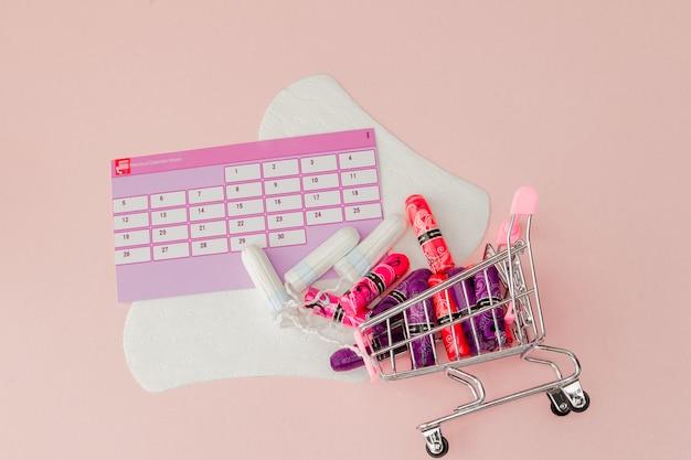 Tamponi, assorbenti femminili e sanitari per giorni critici, calendario femminile, pillole antidolorifiche durante le mestruazioni su sfondo rosa