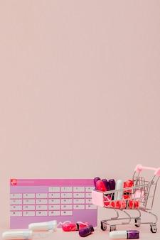 Tamponi, assorbenti femminili e sanitari per giorni critici, calendario femminile, pillole antidolorifiche durante le mestruazioni su una parete rosa. tracciamento del ciclo mestruale e dell'ovulazione