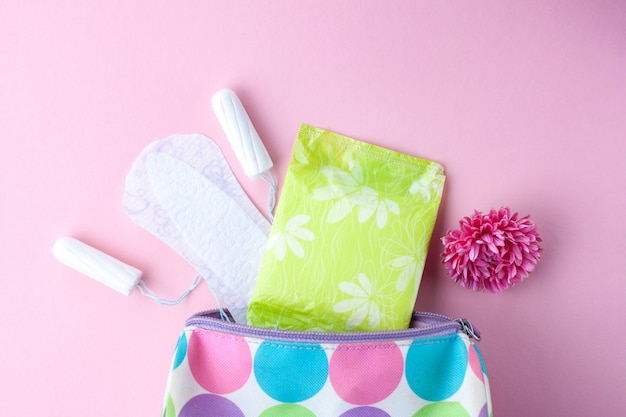 Tamponi, assorbenti femminili, fiori e borsa cosmetica da donna. cura dell'igiene nei giorni critici. ciclo mestruale. prendersi cura della salute delle donne.