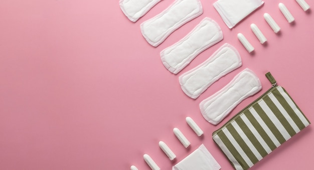 Tamponi, assorbenti femminili su uno sfondo rosa. cure igieniche nei giorni critici. ciclo mestruale.