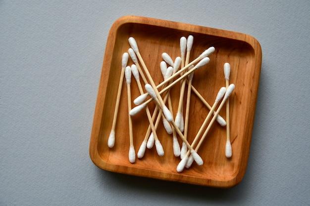 Tamponi di cotone di bambù su un piatto di legno. superficie di carta grigia. concetto di rifiuti zero. vista dall'alto. copia spazio.