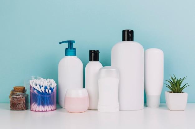 Tamponi di piante e cotone vicino a bottiglie di cosmetici