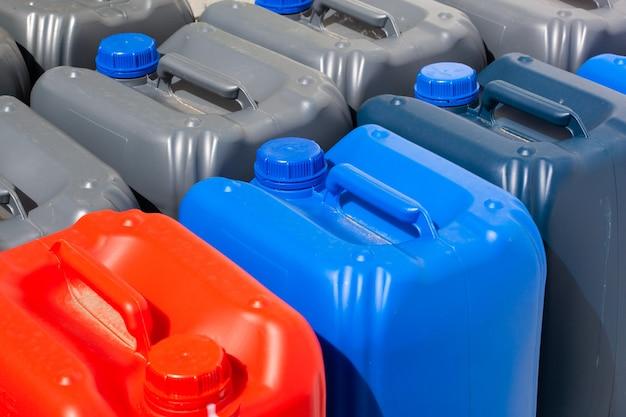 Taniche di plastica di diverso colore in magazzino, produzione, fabbrica. superficie dai contenitori di plastica