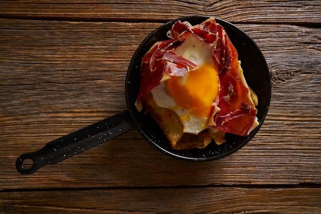 Tapas huevos rotos uova rotte con prosciutto