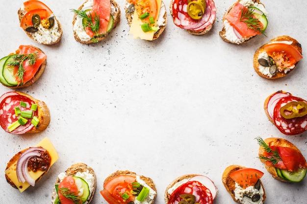 Tapas spagnoli assortiti con pesce, salsiccia, formaggio e verdure. sfondo bianco, vista dall'alto.