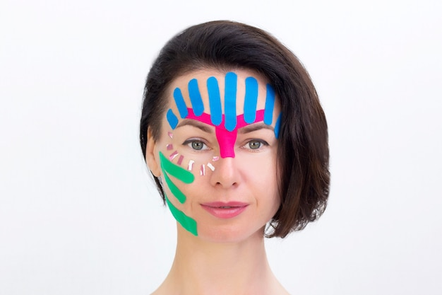 Taping facciale, primo piano del viso di una ragazza con nastro cosmetico antirughe. taping estetico viso.