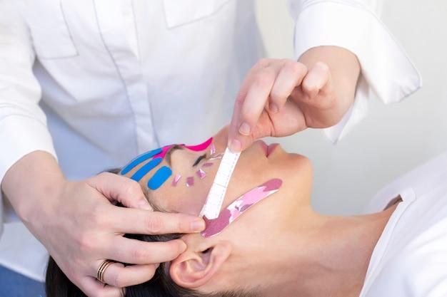 Taping facciale, primo piano del viso di una ragazza con nastro cosmetico antirughe.