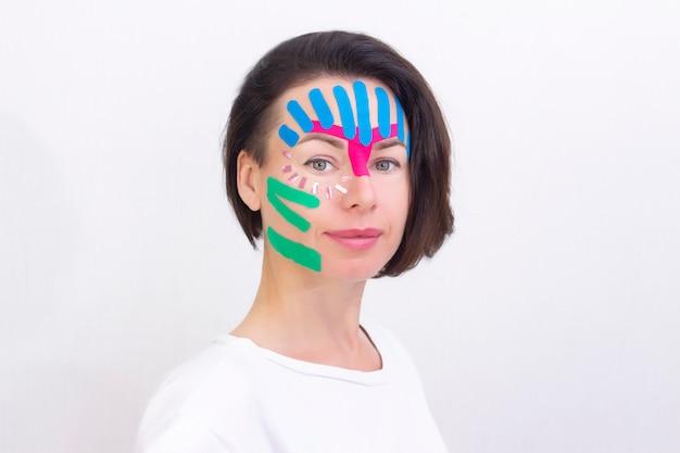 Taping facciale, primo piano del volto di una ragazza con nastro cosmetico antirughe