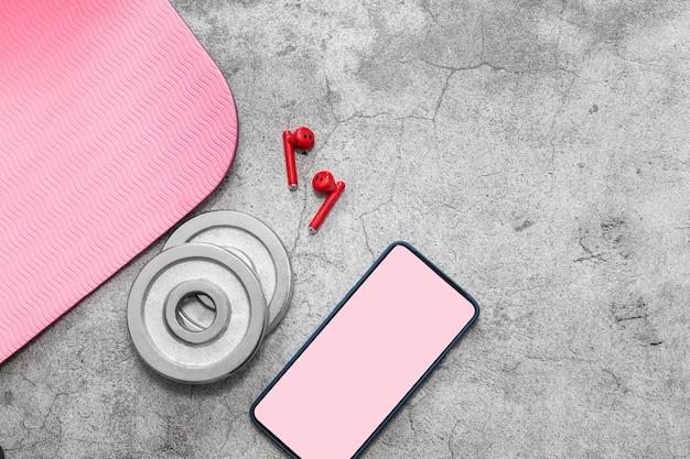 Tappetino fitness, peso con manubri, cuffie wireless, modello di schermo dello smartphone su grigio