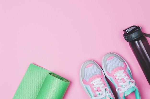 Tappetino yoga, scarpe sportive, bottiglia d'acqua sul rosa