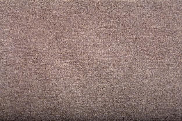 Tappeto che copre lo sfondo. modello e trama del tappeto di colore marrone chiaro. copia spazio