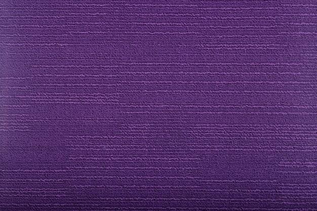 Tappeto che copre lo sfondo. modello e trama del tappeto di colore viola. copia spazio