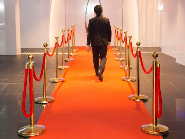 Tappeto rosso tra le barriere della corda nella festa del successo. messa a fuoco selezionata alle barriere di corda.
